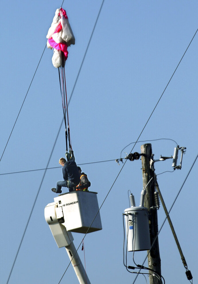 A BASE jumper was rescued from a city of Menomonie bucket truck after he became tangled in guy wires of a 300 ft. tower he jumped from in Menomonie, Wis., on Oct. 17, 2019.  He was arrested for criminal trespass after his parachute got tangled in the guy wires of a cell phone tower in northwestern Wisconsin. Police say the 20-year-old man was illegally jumping from a 300-foot Charter Communications tower in Menomonie Thursday when his chute got tangled in the wires leaving him dangling 50 feet above ground. He called police for help.(Dan Reiland/The Eau Claire Leader-Telegram via AP)