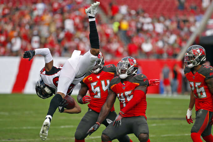 Tampa Bay Buccaneers linebacker Devin White (45) and outside linebacker Lavonte David (54) send Atlanta Falcons wide receiver Russell Gage (83) flying after a reception during the first half of an NFL football game Sunday, Dec. 29, 2019, in Tampa, Fla. (AP Photo/Mark LoMoglio)