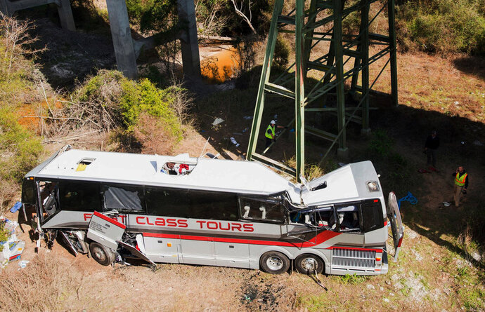 Emergency personnel walk around a bus that crashed into a ravine in Loxley, Ala., Tuesday, March 13, 2018. The bus carrying dozens of students and six adults from Channelview crashed early Tuesday on Interstate 10 nearly the Alabama-Florida line. The driver died and about three dozen others went to hospitals.  (Gregg Pachkowski/Pensacola News Journal via AP)