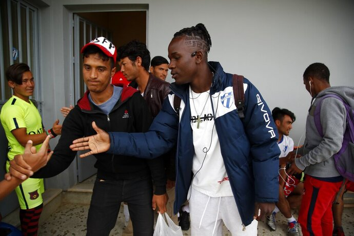 In this Saturday, May 4, 2019, Francis Kalombo from Congo, right, shakes hands with players of Cosmos FC at a soccer field, in Moria village, on the northeastern Aegean island of Lesbos, Greece. A 10-minute walk from Europe's largest refugee camp sits a nondescript yet remarkable soccer field. It's a place where residents of the Moria camp on the Greek island of Lesbos can briefly forget about their tiny container-homes and crowded tents and instead worry about corner kicks and throw-ins. And it's the place where 15-year-old Francis Kalombo became the first refugee to sign for a professional Greek soccer club. (AP Photo/Thanassis Stavrakis)