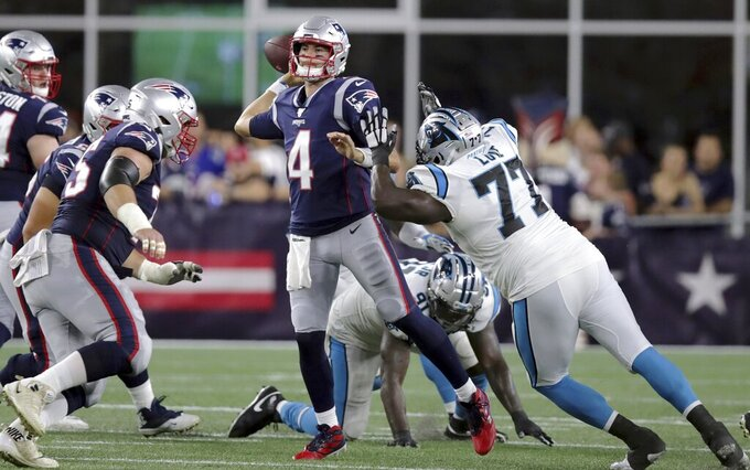 New England Patriots quarterback Jarrett Stidham (4) passes under pressure from Carolina Panthers defensive tackle Kyle Love (77) in the first half of an NFL preseason football game, Thursday, Aug. 22, 2019, in Foxborough, Mass. (AP Photo/Charles Krupa)