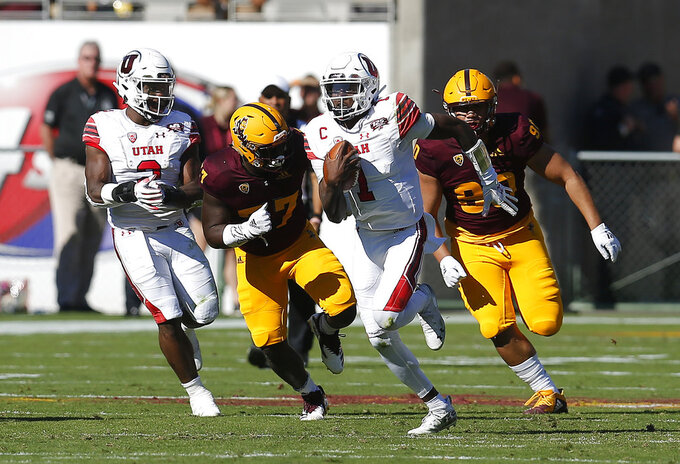 Utah quarterback Tyler Huntley (1) runs away from Arizona State defenders in the first half during an NCAA college football game, Saturday, Nov. 3, 2018, in Tempe, Ariz. (AP Photo/Rick Scuteri)