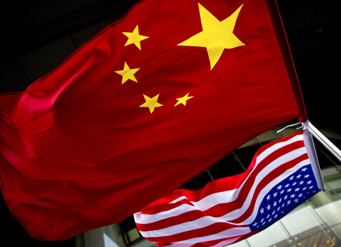 In this Nov. 7, 2012 photo, U.S. and Chinese national flags are hung outside a hotel during the U.S. Presidential election event, organized by the U.S. embassy in Beijing. Government-linked Chinese hackers have intercepted the text messages of thousands of foreigners by penetrating a telecommunications provider and planting eavesdropping software on its servers, the cybersecurity firm FireEye says. (AP Photo/Andy Wong, File)