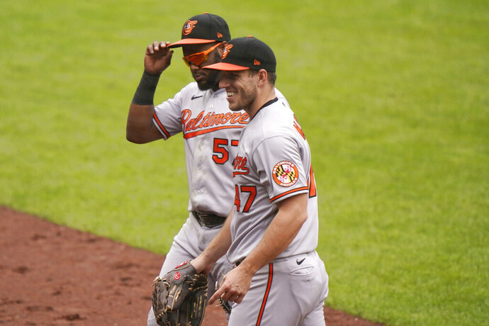 Baltimore Orioles starting pitcher John Means, right, smiles as he heads to the dugout with second baseman Hanser Alberto (57) after the first inning of a baseball game against the New York Yankees, Sunday, Sept. 13, 2020, at Yankee Stadium in New York. (AP Photo/Kathy Willens)