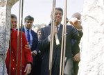 In this Wednesday, Sept. 12, 1990 file photo, former U.S. President Ronald Reagan, center, uses a hammer and chisel on the defunct Berlin Wall to take symbolic swings at the old Cold War barrier, three years after he called the Soviets to tear down the wall in Berlin, Germany. The U.S. Embassy in Berlin is unveiling the statue of Ronald Reagan as a tribute to the 30th anniversary of the fall of the Berlin Wall. The larger-than-life statue is being installed Friday atop the embassy's terrace, at eye-level with the landmark Brandenburg Gate in downtown Berlin. (AP Photo)