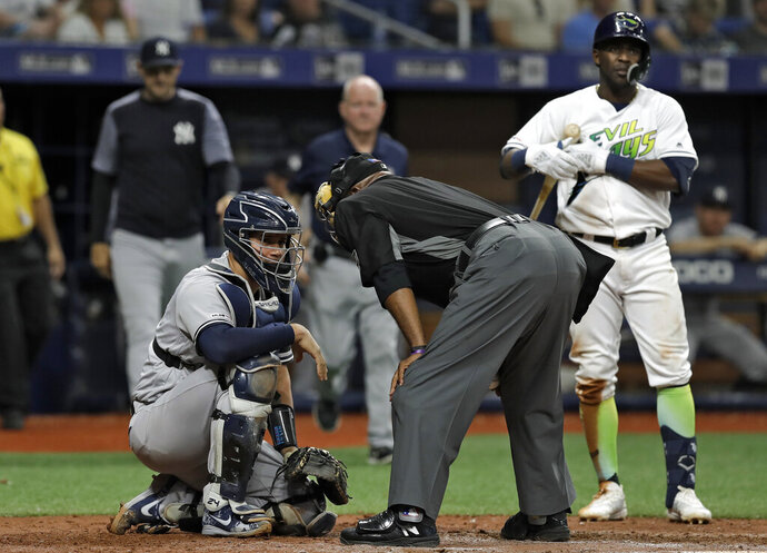 Home plate umpire Laz Diaz, center, talks to New York Yankees catcher Gary Sanchez, left, after he was hit on the head on a swing by Tampa Bay Rays' Guillermo Heredia, right, during the eighth inning of a baseball game Saturday, May 11, 2019, in St. Petersburg, Fla. Sanchez stayed in the game. (AP Photo/Chris O'Meara)