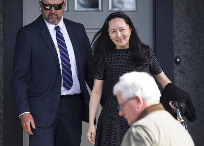 FILE - In this May 8, 2019, file photo, Huawei Chief Financial Officer Meng Wanzhou, back right, who is out on bail and remains under partial house arrest leaves her home to attend a court appearance in Vancouver, British Columbia. China on Thursday, Sept. 5, 2019, has urged Canada to