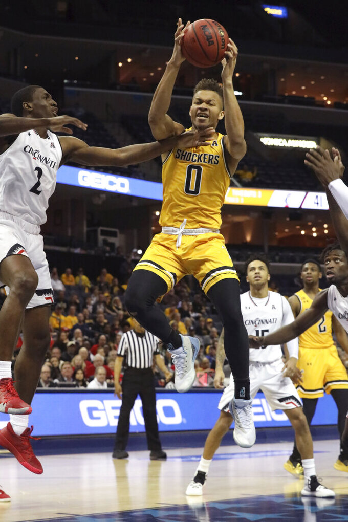 Wichita State's Dexter Daniels goes for the goal as Cincinnati player Keith Williams defends in the first half of an NCAA college basketball game at the American Athletic Conference tournament Saturday, March 16, 2019, in Memphis, Tenn. (AP Photo/Troy Glasgow)