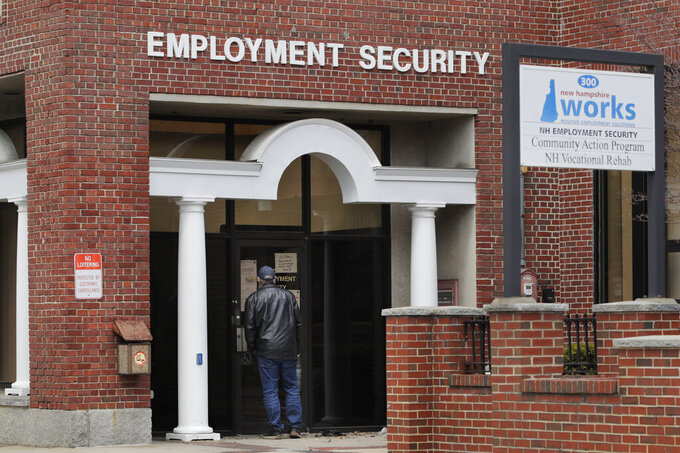 A man reads a note on a locked door at the New Hampshire Employee Security center, which handles unemployment claims, in Manchester, N.H., Thursday, April 16, 2020. Due to the virus outbreak, a note on the office door requested that all claims be handled remotely either on the phone or online. (AP Photo/Charles Krupa)