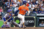 Houston Astros' Kyle Tucker watches his RBI single in front of Texas Rangers catcher Jose Trevino during the second inning of a baseball game Friday, May 14, 2021, in Houston. (AP Photo/Michael Wyke)