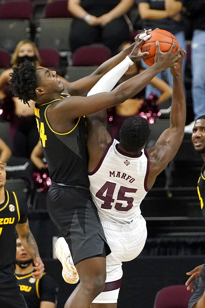 Missouri forward Kobe Brown (24) fights for a rebound with Texas A&M forward Kevin Marfo (45) during the first half of an NCAA college basketball game Saturday, Jan. 16, 2021, in College Station, Texas. (AP Photo/Sam Craft)