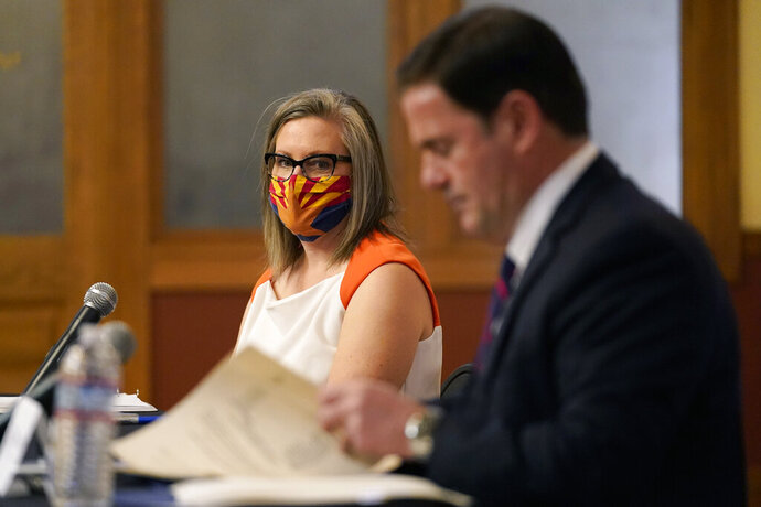 Arizona Secretary of State Katie Hobbs, left, watches as Arizona Gov. Doug Ducey signs election documents to certify the election results for federal, statewide, and legislative offices and statewide ballot measures at the official canvass at the Arizona Capitol Monday, Nov. 30, 2020, in Phoenix. (AP Photo/Ross D. Franklin, Pool)