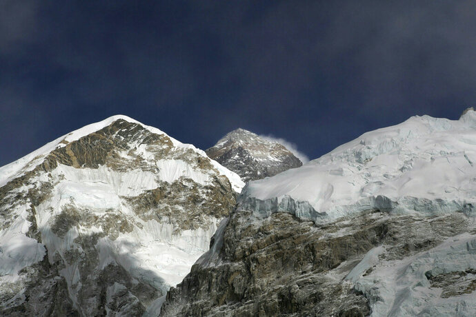 FILE - In this March 7, 2016, file photo, Mt. Everest, in middle, altitude 8,848 meters (29,028 feet), is seen on the way to base camp. American climber Don Cash who fulfilled his dream of climbing the highest mountains on each of the seven continents by reaching the summit of Mount Everest died of probable altitude sickness on the way down, mountaineering officials said Friday, May 24, 2019. Cash became ill at the summit and was treated there by his two Sherpa guides, one of the officials said. (AP Photo/Tashi Sherpa, File)