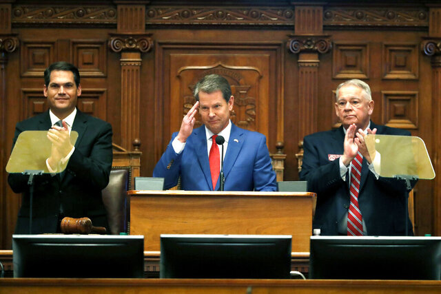 FILE - In this Jan. 16, 2020 file photo, Gov. Brian Kemp, center, is flanked by House Speaker David Ralston, R-Blue Ridge, right, and Lt. Gov. Geoff Duncan as he salutes former U.S. Senator Johnny Isakson, R-Ga., during the State of the State address before a joint session of the Georgia General Assembly in Atlanta. Kemp is proposing that Georgia borrow almost $900 million for construction projects and equipment next year. Key projects in the Republican governor's borrowing plan include $70 million to expand the state-owned convention center in Savannah and $55 million to build a new headquarters for the Department of Public Safety in Atlanta.  (AP Photo/John Bazemore, File)