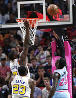 Miami Heat guard Kendrick Nunn (25) shoots over Golden State Warriors guard Jordan Poole (3) and forward Draymond Green (23) during the first half of an NBA basketball game, Friday, Nov. 29, 2019, in Miami. (AP Photo/Lynne Sladky)