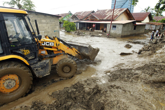 A heavy machinery clears up mud from a neighborhood following a flood in Dili, East Timor, Monday, April 5, 2021. Multiple disasters caused by torrential rains in eastern Indonesia and neighboring East Timor have left a number of people dead or missing as rescuers were hampered by damaged bridges and roads and a lack of heavy equipment Monday. (AP Photo/Kandhi Barnez)