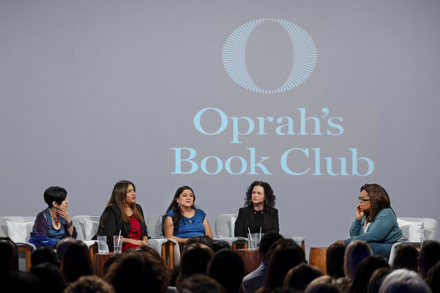 In this Feb. 13, 2020 photo released by Apple, Oprah Winfrey, right, hosts a taping of Oprah's Book Club with Jeanine Cummins, author of
