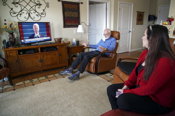Democrat Jim Carpenter, left, and Republican Natalie Abbas watch the inauguration of President Joe Biden in Carpenter's apartment in Frederick, Md., on Wednesday, Jan. 20, 2021. The two are local ambassadors for a program designed to bridge the nation's extraordinary political divide. (AP Photo/Allen G. Breed)
