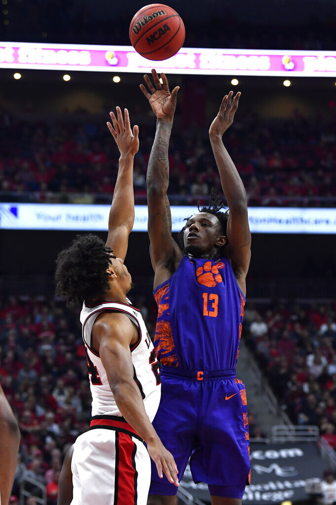 Clemson guard Tevin Mack (13) shoots over Louisville forward Dwayne Sutton (24) during the first half of an NCAA college basketball game in Louisville, Ky., Saturday, Jan. 25, 2020. (AP Photo/Timothy D. Easley)