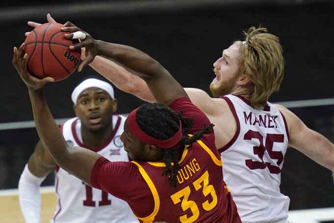 Iowa State forward Solomon Young (33) pulls in a rebound next to Oklahoma forward Brady Manek (35) during the first half of an NCAA college basketball game in the first round of the Big 12 men's tournament in Kansas City, Mo., Wednesday, March 10, 2021. (AP Photo/Orlin Wagner)