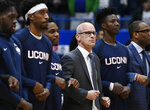 FILE - In this Dec. 2, 2018, file photo,  Connecticut head coach Dan Hurley, center, stands with his players during the national anthem before an NCAA college basketball game in Hartford, Conn. Hurley is hopeful that recently passed legislation in Connecticut allowing college athletes to profit from the use of their names, images and likenesses will keep more players in school. (AP Photo/Jessica Hill, File)