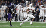 FILE - In this Dec. 28, 2017, file photo, Stanford running back Bryce Love (20) is pursued by TCU cornerback Jeff Gladney (12) as he runs for a touchdown during the second half of the Alamo Bowl NCAA college football game, in San Antonio. Love bucked popular opinion by sticking with the Cardinal rather than declaring early for the NFL draft.(AP Photo/Eric Gay, File)