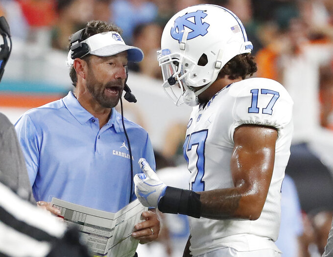 North Carolina head coach Larry Fedora., left, talks with wide receiver Anthony Ratliff-Williams (17) during the first half of an NCAA college football game against Miami, Thursday, Sept. 27, 2018, in Miami Gardens, Fla. (AP Photo/Wilfredo Lee)