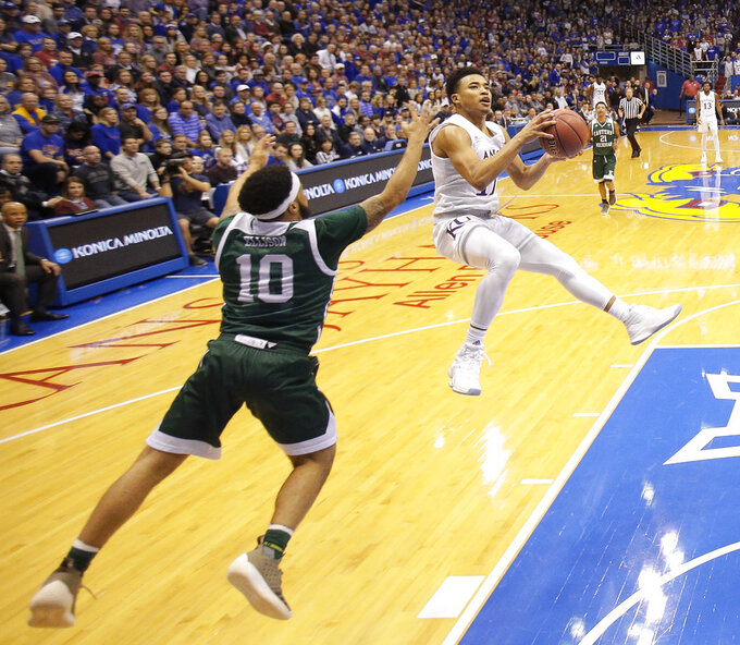Kansas' Devon Dotson, right, shoots under pressure from Eastern Michigan's Malik Ellison (10) during the first half of an NCAA college basketball game Saturday, Dec. 29, 2018, in Lawrence, Kan. (AP Photo/Charlie Riedel)