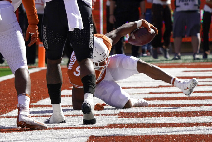 Texas running back Bijan Robinson (5) rolls into the end zone for a touchdown against Oklahoma State during the first half of an NCAA college football game in Austin, Texas, Saturday, Oct. 16, 2021. (AP Photo/Chuck Burton)