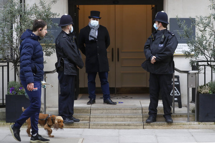 """A man walks by with a dog as police officers stand outside King Edward VII's hospital in London, Tuesday, Feb. 23, 2021. Britain's Prince Philip was admitted to the private King Edward VII's Hospital in London on Tuesday, Feb. 16, after falling ill. Buckingham Palace said the husband of Queen Elizabeth II was expected to remain in the hospital into this week for a period of """"observation and rest."""" (AP Photo/Kirsty Wigglesworth)"""
