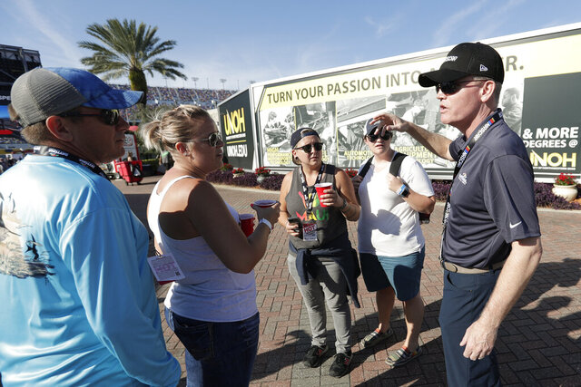 Eric Nyquist, right, a senior vice president and chief communications officer with NASCAR, greets fans in the infield and thanks them for returning for the resumption of the Daytona 500 auto race at Daytona International Speedway, Monday, Feb. 17, 2020, in Daytona Beach, Fla. Sunday's race was postponed because of rain. (AP Photo/John Raoux)