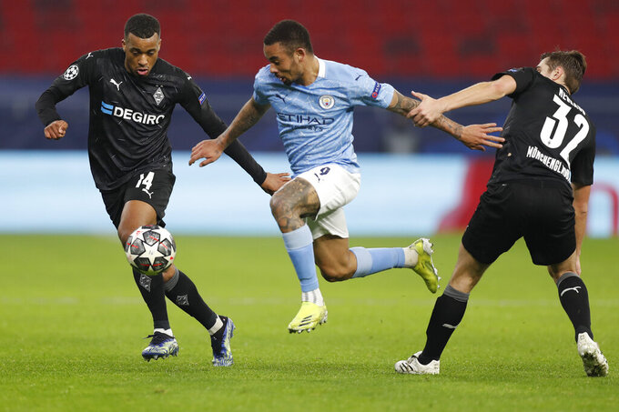 Manchester City's Gabriel Jesus, center, is challenged by Moenchengladbach's Alassane Plea, left and Moenchengladbach's Florian Neuhaus during the Champions League round of 16 first leg soccer match between Borussia Monchengladbach and Manchester City at the Puskas Arena stadium in Budapest, Hungary, Wednesday, Feb. 24, 2021. (AP Photo/Laszlo Balogh)