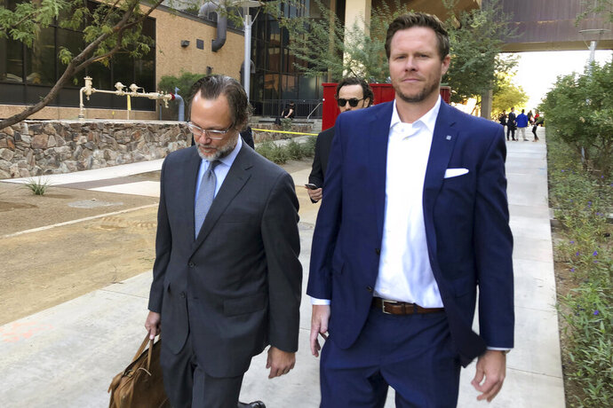 FILE - In this Nov. 5, 2019, file photo,  former Maricopa County Assessor Paul Petersen, right, walks with his attorney, Kurt Altman, as they leave a court hearing in Phoenix. Petersen, who has acknowledged running an adoption scheme in three states that involved women from the Marshall Islands, is required to report to federal prison by midday Thursday, Jan. 21, 2021, to start serving a 6-year sentence for his guilty plea in Arkansas to conspiring to commit human smuggling. Petersen also is awaiting sentencing for related convictions in Arizona and in Utah. (AP Photo/Jacques Billeaud, File)