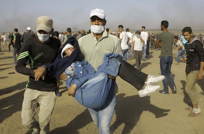 Palestinian medics and protesters evacuate a wounded youth near the Gaza Strip's border with Israel, during a protest east of Khan Younis, in the Gaza Strip, Friday, June 8, 2018. (AP Photo/Adel Hana)