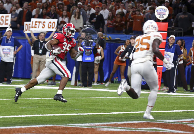 Georgia running back Brian Herrien (35) runs for a touchdown as Texas defensive back B.J. Foster (25) moves toward him during the first half of the Sugar Bowl NCAA college football game in New Orleans, Tuesday, Jan. 1, 2019. (AP Photo/Rusty Costanza)