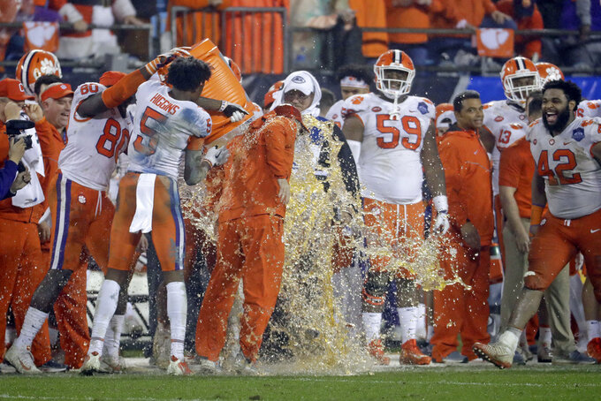 Players dunk Clemson head coach Dabo Swinney, center, in the closing moments of the second half of the Atlantic Coast Conference championship NCAA college football game against Pittsburgh in Charlotte, N.C., Saturday, Dec. 1, 2018. (AP Photo/Chuck Burton)