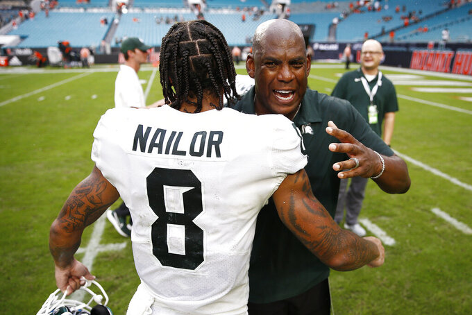 Michigan State head coach Mel Tucker hugs wide receiver Jalen Nailor (8) after they defeated Miami in an NCAA college football game, Saturday, Sept. 18, 2021, in Miami Gardens, Fla. (AP Photo/Michael Reaves)