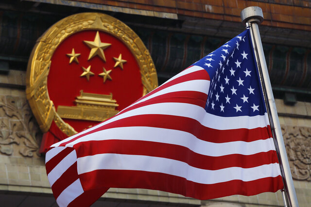 FILE - In this Nov. 9, 2017, file photo, an American flag is flown next to the Chinese national emblem during a welcome ceremony for visiting U.S. President Donald Trump outside the Great Hall of the People in Beijing. U.S. and Chinese trade envoys discussed strengthening coordination of their government's economic policies during a phone meeting, the Ministry of Commerce announced. (AP Photo/Andy Wong, File)