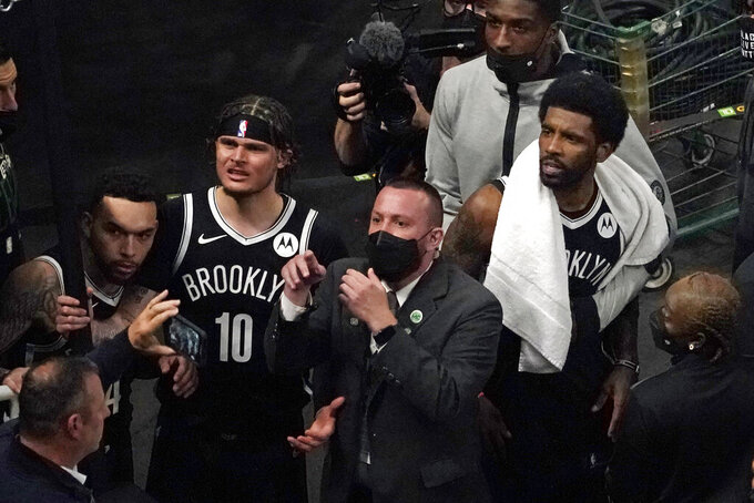 A security guard points as Brooklyn Nets' Kyrie Irving, right with towel, and teammates look up at a fan who reportedly threw a water bottle at him as he left the court after Game 4 during an NBA basketball first-round playoff series, Sunday, May 30, 2021, in Boston. (AP Photo/Elise Amendola)
