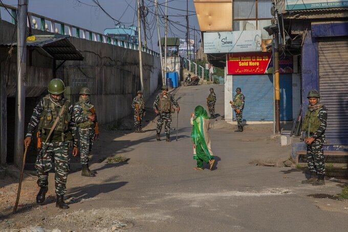 A Kashmiri woman covers her face with a scarf as she walks past paramilitary soldiers standing guard in a closed market area in Srinagar, Indian controlled Kashmir, Friday, Sept. 3, 2021. Indian authorities cracked down on public movement and imposed a near-total communications blackout in disputed Kashmir on Thursday after the death of Syed Ali Geelani, a top separatist leader who became the emblem of the region's defiance against New Delhi. (AP Photo/ Dar Yasin)