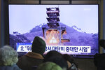 People watch a TV screen showing a file image of a ground test of North Korea's rocket engine during a news program at the Seoul Railway Station in Seoul, South Korea, Monday, Dec. 9, 2019. North Korea said Sunday it carried out a