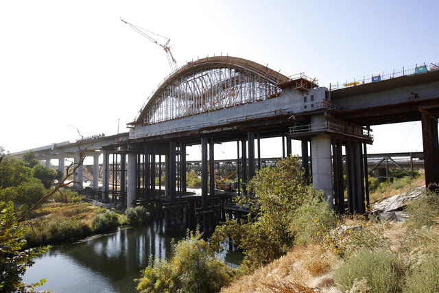 FILE - This Oct. 9, 2019 file photo shows the high speed rail viaduct under construction over the San Joaquin River near Fresno, Calif. The California High-Speed Rail Authority is bumping its overall cost estimate for completing the rail line between San Francisco and Los Angeles to more than $80 billion. (AP Photo/Rich Pedroncelli, File)