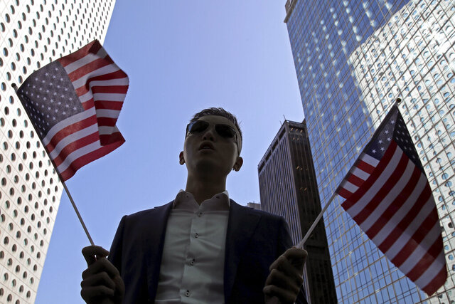 A protester holds American flags during a demonstration in Central, the financial district of Hong Kong, Thursday, Nov. 28, 2019. China reacted furiously to President Donald Trump's signing of two bills on Hong Kong human rights and said the U.S. will bear the unspecified consequences. A foreign ministry statement Thursday repeated heated condemnations of the laws and said China will counteract. It said all the people of Hong Kong and China oppose the move. (AP Photo/Kin Cheung)