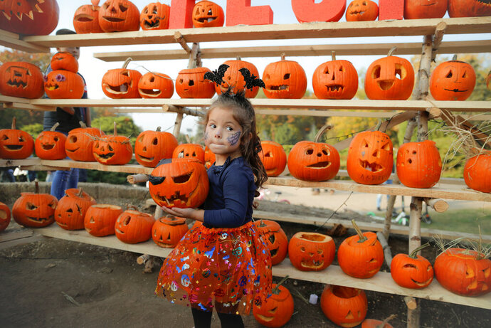 In this Saturday, Oct. 26, 2019 photo a little girl carries the pumpkin she carved in Bucharest, Romania. The Halloween Pumpkin Fest,