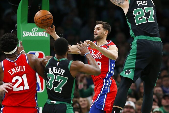 Philadelphia 76ers' Raul Neto (19) passes the ball as Boston Celtics' Semi Ojeleye (37) and Daniel Theis (27) defend during the first half of an NBA basketball game in Boston, Saturday, Feb. 1, 2020. (AP Photo/Michael Dwyer)