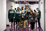 Michigan State guard Matt McQuaid, left, guard Cassius Winston, forward Aaron Henry, forward Xavier Tillman and forward Kenny Goins walk to an NCAA men's college basketball individual news conferences in Washington, Saturday, March 30, 2019. Michigan State plays Duke in the East Regional final game on Sunday. (AP Photo/Alex Brandon)