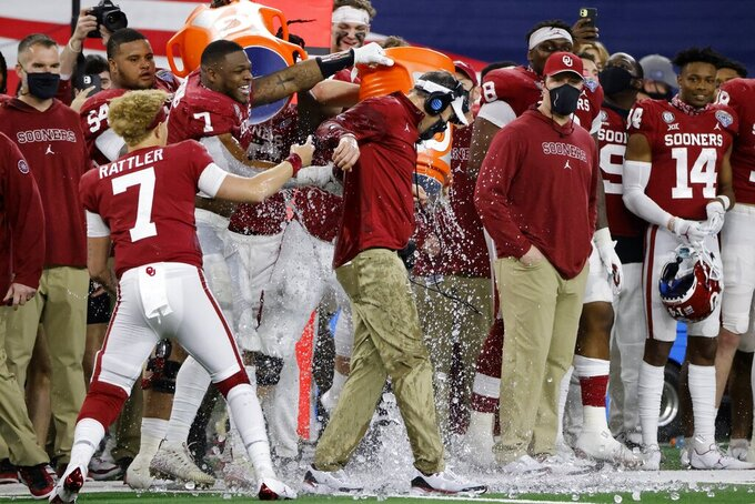 Oklahoma quarterback Spencer Rattler (7) watches as defensive end Ronnie Perkins (7) douses coach Lincoln Riley, center, in the closing seconds of the team's Cotton Bowl NCAA college football game against Florida in Arlington, Texas, Wednesday, Dec. 30, 2020. Oklahoma won 55-20. (AP Photo/Michael Ainsworth)