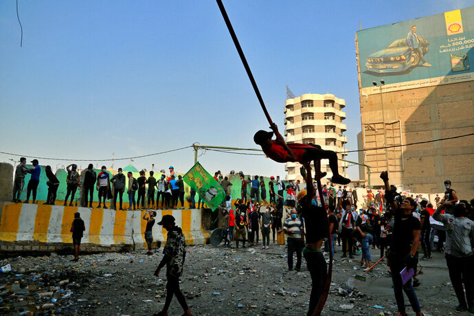 An anti-government protester swings from a cable during ongoing demonstrations, in Baghdad, Iraq, Wednesday, Nov. 13, 2019. Protesters say an intensifying crackdown by Iraqi authorities is instilling fears but remain defiant with calls for millions to return to the streets this week. (AP Photo/Hadi Mizban)