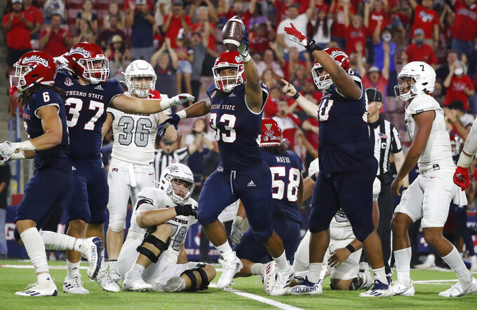 Fresno State defensive end Kwami Jones holds the ball up in celebration of a sack and fumble that lead to a victory against UNLV during the second half of an NCAA college football game in Fresno, Calif., Friday, Sept. 24, 2021. (AP Photo/Gary Kazanjian)
