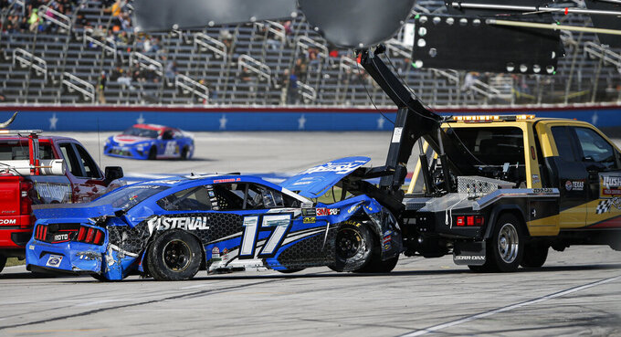 Ricky Stenhouse Jr.'s car is towed to the garages after a wreck exiting turn four and ending in the grass on the front stretch during a NASCAR auto race at Texas Motor Speedway, Sunday, Nov. 3, 2019, in Fort Worth, Texas. (AP Photo/Brandon Wade)